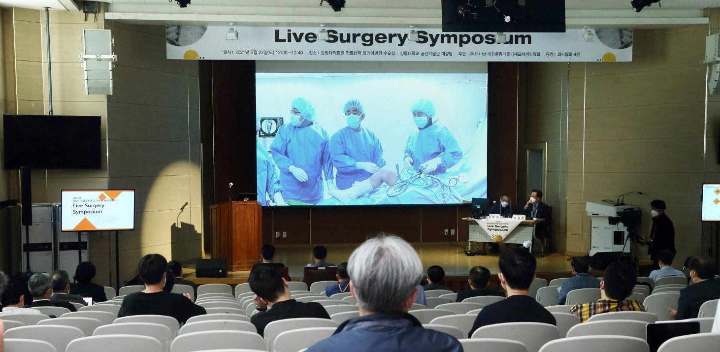 경희대학교병원 정형외과 윤경호 교수가 2021년 5월 22일 개최된 제6회 대한운동계줄기세포재생의학회 라이브 서저리(Live Surgery) 심포지엄에서, 카티라이프 수술을 라이브로 진행하며 수술 과정 및 노하우를 전달하고 있다.